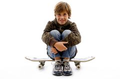 Front view of boy sitting on skateboard Stock Images