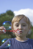 Front view of a boy with soap bubbles. Royalty Free Stock Image