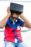 Front view of boy using virtual reality headset in classroom. Front view of boy using virtual reality headset while sitting in classroom Royalty Free Stock Image