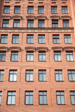 Front view of brick wall contemporary apartment building with windows Stock Image