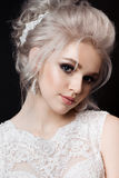 Front view of bride wearing lace dress, earrings with shiny diamonds posing at camera in dark studio. Gorgeous blonde woman with s Stock Image