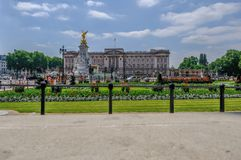 Front view of Buckingham Palace with Memorial Gardens in front a. London, UK - June 8, 2018: Front view of Buckingham Palace with Queen Victoria`s Memorial and Royalty Free Stock Images
