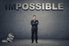 Front view of a buisnessman standing with folded arms under big 3d concrete word 'possible'. Nothing is impossible. Unlimited opportunities. Progressive ideas Stock Image