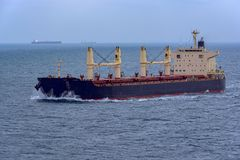 Front view of bulk carrier vessel. Front view of bulk carrier vessel sailing through rough sea to Singapore strait royalty free stock photo