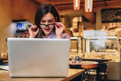 Front view. Business woman is sitting in cafe in front of laptop and looks at screen in surprise, lowering her glasses. Front view. Young business woman is Stock Photo