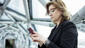 Front view of a business woman walkistanding checking smart phone content and then stops. She is scrolling a monitor of. The smartphone. She stands wearing stock video