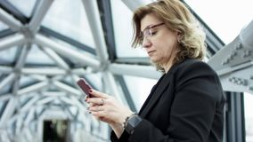 Front view of a business woman walkistanding checking smart phone content and then stops. She is scrolling a monitor of. The smartphone. She stands wearing stock video footage