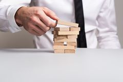 Front view of businessman building a tower of wooden pegs stock photos
