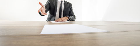 Front view of a businessman sitting at his desk with document or Royalty Free Stock Photos