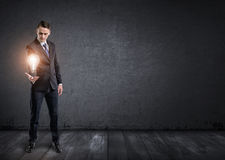 Front view of businessman standing and holding glowing light bulb in his hand Royalty Free Stock Image