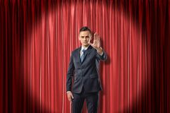Front view of businessman standing in spotlight against red stage curtain looking at camera and holding out hand with stock photo