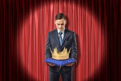 Front view of businessman standing in spotlight against red stage curtain looking down at gold crown on blue pillow stock images