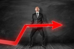 Front view of businessman standing and trying to lift up red graph arrow near black graph ruled wall. stock photos