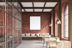 Front view of cafe with chairs, brick. Front view of cafe with chairs standing near small round tables and a sofa near a brick wall with a poster hanging above Royalty Free Stock Photos