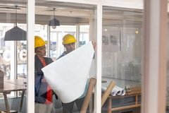 Architects discussing over blueprint in a modern office. Front view of Caucasian architects discussing over blueprint in a modern office royalty free stock photography
