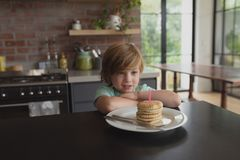 Boy with food sitting at dining table at home. Front view of Caucasian boy with food sitting at dining table in a comfortable home royalty free stock photos