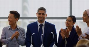 Businessman standing on the podium with his colleagues in the business seminar 4k. Front view of a Caucasian businessman standing on the podium with his stock footage