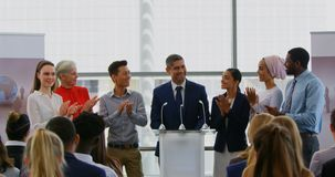 Businessman standing on the podium with his colleagues in the business seminar 4k. Front view of a Caucasian businessman standing on the podium with his stock video