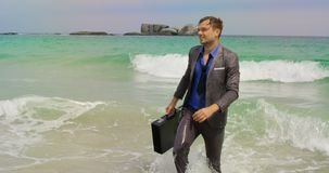 Front view of Caucasian Businessman walking with briefcase in the sea at beach 4k. Front view of Caucasian Businessman walking with briefcase in the sea at beach stock video footage