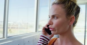 Front view of Caucasian Businesswoman talking on mobile phone in the office 4k stock footage