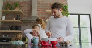 Father and daughter preparing cookie on worktop in kitchen at home 4k. Front view of Caucasian father and daughter preparing cookie on worktop in kitchen at home stock video