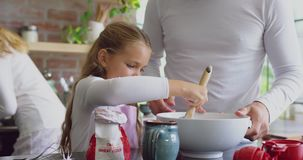 Father and daughter preparing cookie on worktop in kitchen at home 4k. Front view of Caucasian father and daughter preparing cookie on worktop in kitchen at home stock video footage
