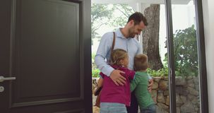 Father embracing his children at door in a comfortable home 4k. Front view of Caucasian father embracing his children at door in a comfortable home. They are stock footage