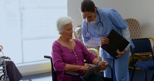 Front view of Caucasian female doctor and senior woman discussing over digital tablet at nursing hom