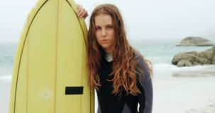 Front view of Caucasian female surfer standing with surfboard on the beach 4k