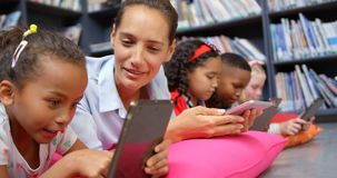 Front view of Caucasian female teacher and school kids studying on digital tablet in the schoo 4k stock footage