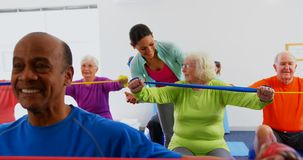 Front view of Caucasian female trainer training senior woman in exercise at fitness studio 4k. Front view of Caucasian female trainer training senior woman in stock video footage