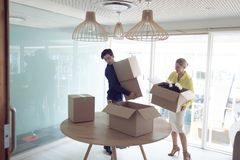 Male and female executives holding cardboard boxes in office. Front view of Caucasian male and female office executives holding cardboard boxes in office royalty free stock image