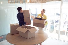 Male and female executives holding cardboard boxes in office. Front view of Caucasian male and female office executives holding cardboard boxes in office stock photos