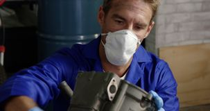 Male mechanic repairing motorbike engine in repair garage 4k. Front view of Caucasian male mechanic repairing motorbike engine in repair garage. He is wearing stock footage