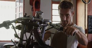 Male mechanic repairing motorbike in repair garage 4k. Front view of Caucasian male mechanic repairing motorbike in repair garage. He is fixing motorbike brake stock footage