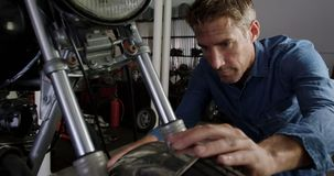 Male mechanic repairing motorbike in repair garage 4k. Front view of Caucasian male mechanic repairing motorbike in repair garage. He is fixing motorcycle front stock footage