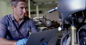 Male mechanic using laptop in motorbike repair garage 4k. Front view of Caucasian male mechanic using laptop in motorbike repair garage. He is looking at stock video footage