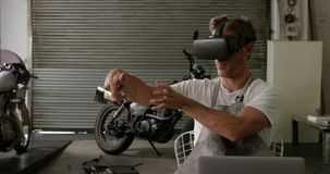 Front view of Caucasian male mechanic using virtual reality headset in motorbike repair garage 4k. Front view of Caucasian male mechanic using virtual reality stock video
