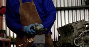 Male mechanic working in repair garage 4k. Front view of Caucasian male mechanic working in repair garage. He is using angle grinder 4k stock video footage
