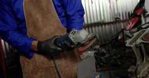 Male mechanic working in repair garage 4k. Front view of Caucasian male mechanic working in repair garage. He is using angle grinder 4k stock footage