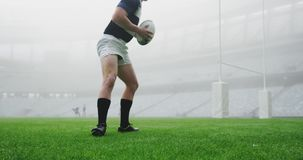 Male rugby player tying shoelaces in the stadium 4k. Front view of Caucasian male rugby player tying shoelaces in the stadium. He is running with rugby ball 4k stock video footage