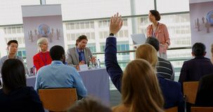 Caucasian male speaker questioning the public in a business seminar 4k. Front view of a Caucasian male speaker sitting at the speaker table and questioning the stock video footage