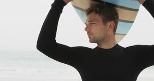 Front view of Caucasian male surfer carrying surfboard on his head at beach 4k