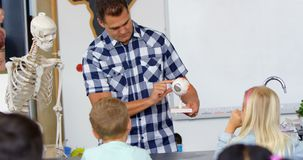 Front view of Caucasian male teacher explaining model in the classroom  4k stock footage