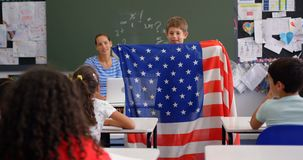 Front view of Caucasian schoolboy explaining about American flag in the classroom 4k stock video footage