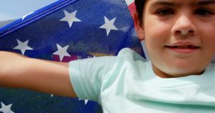 Front view of Caucasian schoolboy holding American flag in school playground 4k stock footage