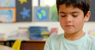 Front view of Caucasian schoolboy sitting at desk in classroom at school 4k stock footage