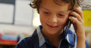 Front view of Caucasian schoolboy talking on mobile phone in classroom at school 4k. Front view of Caucasian schoolboy talking on mobile phone in classroom at stock video footage