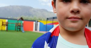 Front view of Caucasian schoolboy wrapped in American flag in school playground 4k stock video footage