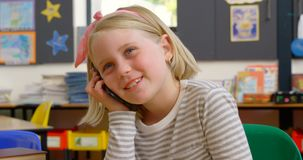 Front view of Caucasian schoolgirl talking on mobile phone at desk in classroom 4k. Front view of Caucasian schoolgirl talking on mobile phone at desk in stock video footage